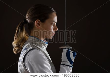 Young Woman Fencer Holding The Sword In Front Of Her
