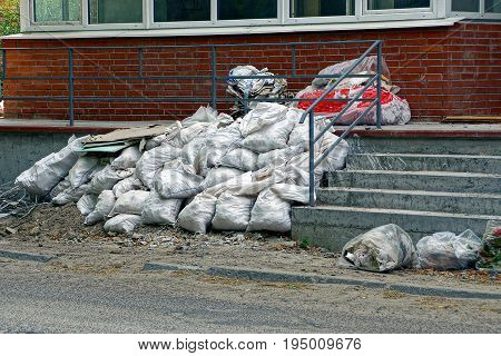 A pile of garbage from full white sacks near the threshold