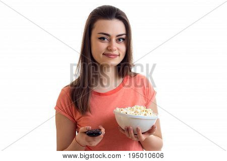 smiling pretty girl holding a remote control and a plate pop corn isolated on white background