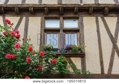 Window of the old house decorated with flowers Cognac France