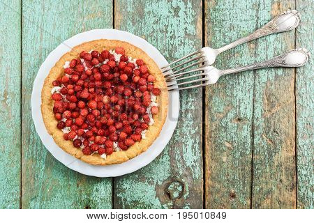 Fresh forest strawberry tart with cottage cheese with vintage melchior forks overhead view