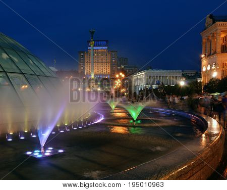 Illuminated Maidan Nezalezhnosti square (Kiev). Fountains in foreground.