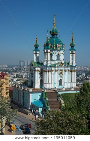 Saint Andrew's Church (Kiev) against blue sky background. Blossom tree in foreground.