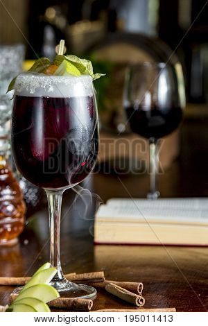 Red wine sangria on the bar with dry ice and fruits for decoration