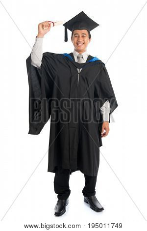 Full body attractive Southeast Asian male university student in graduation gown holding paper certificate, standing isolated on white background.