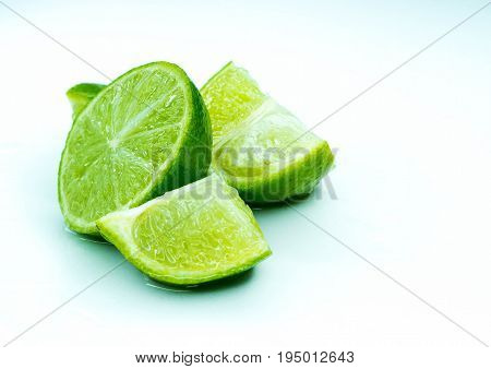 Pieces of ripe juicy lime in a section. Sliced juicy lime on a white background