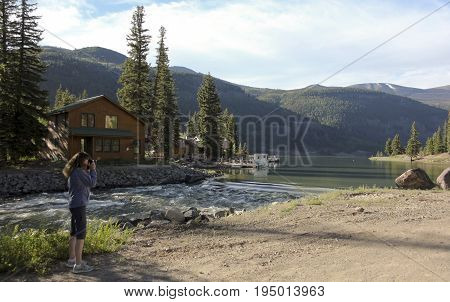 LAKE CITY, COLORADO, JUNE 20. The Alpine Loop Backcountry Byway on June 20, 2017, near Lake City, Colorado. A Woman Shoots Lake Photos on the Alpine Loop Backcountry Byway in Colorado.