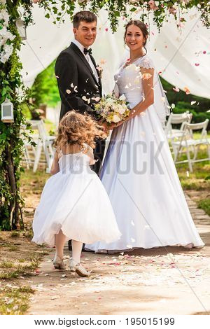 Bride and groom on the wedding ceremony. Adorable girl showered the newlyweds with flying rose petals