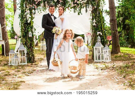 Bride and groom are smiling after wedding ceremony. Adorable children with flying rose petals in baskets