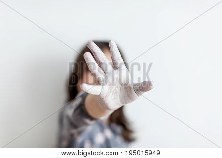 Silhouette young girl with her hand extended signaling to stop. Concept of human rights