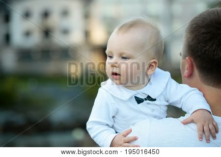 Cute baby boy small little child with blue eyes and blond hair in arms of father on sunny summer day outdoors in white shirt on blurred natural background. Newborn son and dad family love