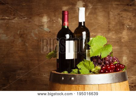 Bottles of wine on the oak barrel over old shabby wooden background