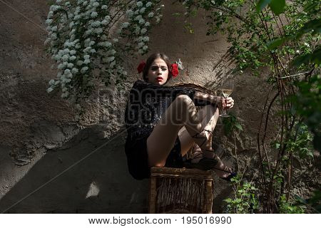 woman or cute girl fashion model with red lips makeup and wine glass sitting on wicker chair in yard on outdoor wall. Alcohol drinking. Enjoying life. Holiday celebration. Spring summer