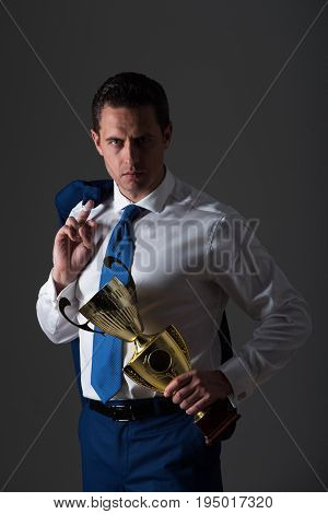 man champion confident businessman or manager holding golden winner cup in fashion white shirt blue tie and jacket on shoulder on grey background. Business and success. Victory and trophy