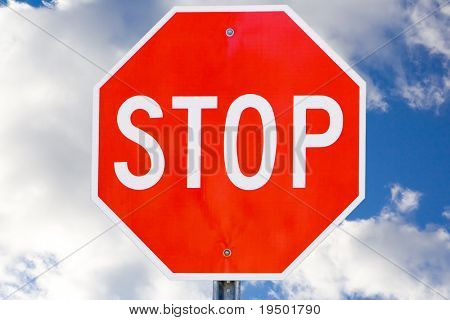 Stop Sign Against Blue Sky and Clouds