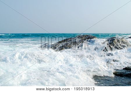 The sea wave is crashed about the shore and rocks