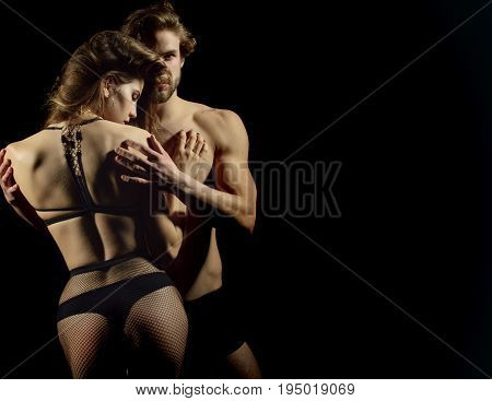 Man and woman in sexy underwear. Couple in love. Macho with muscle biceps triceps hugging sexi girl in fishnet pantyhose on black background. Erotic and desire copy space