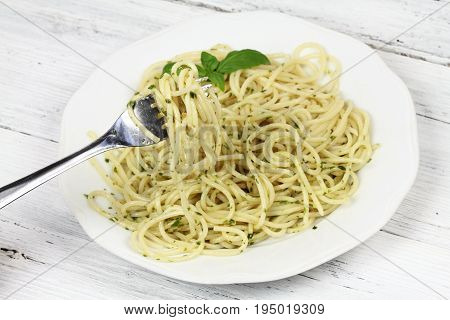 Spaghetti with homemade pesto and basil on white table