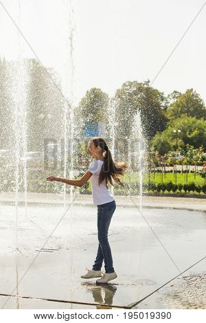 Teenage girl get fun in public city fountain on a very hot day