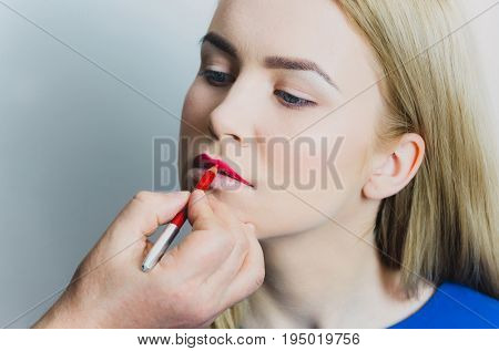 Male Hand Applying Red Pencil On Woman Lips