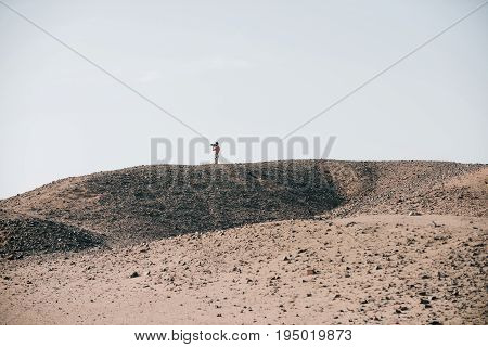 Man shooting with camera on desert hill with grey sand surface and rocky texture on white sky. Barchans dunes and arid landscape. Hobby. Active leisure. Travel and travelling. Wanderlust