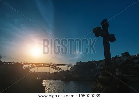 Dom Luis I bridge in backlit at sunset with the cross in an abandoned chapel in the foreground, Porto, Portugal.