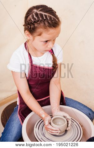 Girl makes pottery from white clay on a potter's wheel