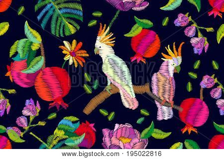 Seamless vector pattern with cockatoo parrots, fruits, palm leaves and flowers. Embroidered texture. Vintage textile collection.