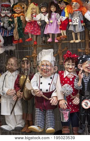 PRAGUE CZECH REPUBLIC - APRIL 30 2017: Traditional colorful puppets made of wood in shop.In Prague there are many gift shops selling colorful puppets these are characters from films historical characters and other