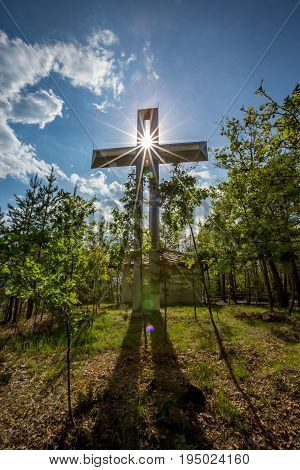 Cross with a Bright Blue Sky and Sun. Diffraction effect. Pine trees surrounding.