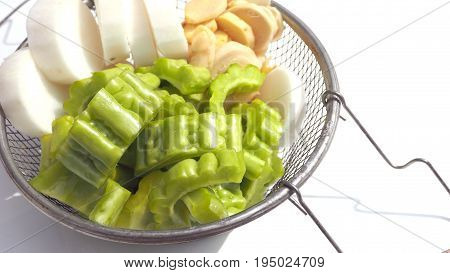 Gourd with Ginger and Chinese radishare raw herb for cooking soup are in aluminum sieve on white background has copy space.
