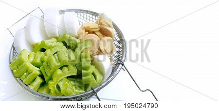 Raw vegetable are gourd and Chinese radish with Ginger in a sieve on white background and has copy space.