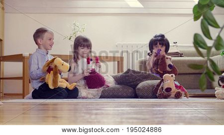 A group of children sitting on the floor and playing stuffed toys. Two girls and boy. One girl looks upset