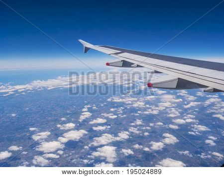 View from a plane window: a plane wing over clouds and blue sky. Traveling by air. Airplane flying above earth at 10000 m -50 °C (-58.0 °F).
