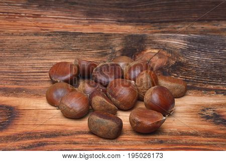 Chestnuts on wooden background. Group of chestnuts. Chestnuts - fruits horse chestnut - Aesculus hippocastanum.