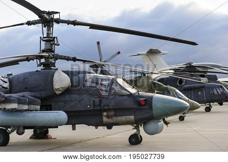 Helicopters and planes in row, military copters and reconnaissance aircrafts, air force, modern army aviation and aerospace industry, dramatic clouds on background