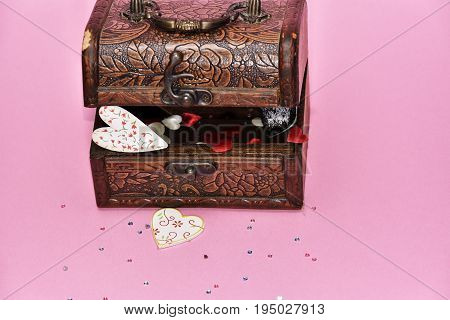 hearts in a treasure chest. Valentine's Day gift chest with treasure and heart decoration on wooden