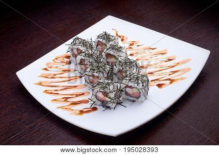 Set of sushi maki on white plate. Japanese food isolated on background