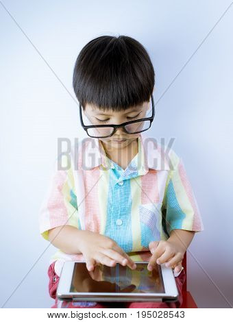 Nerdy Asian kid is playing education game on tablet on white background