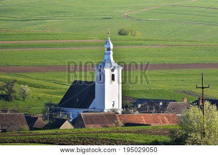 View of white church in a village. Aita Seaca Covasna. Romania
