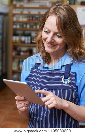 Delicatessen Owner In Store With Digital Tablet