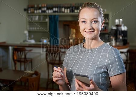 Portrait Of Waitress With Notepad In Restaurant