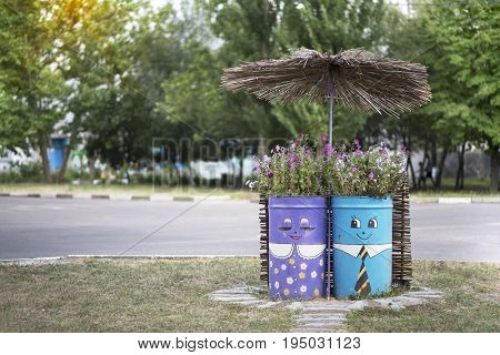 Skadovsk Ukraine - June 23 2017: Two painted barrels with flowers under the umbrella exterior opposite the cafe Bucket street decoration set