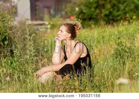 Attractive young sad woman sitting on grass