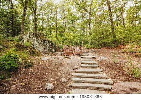 Two wooden armchairs in the park. stone steps at the place of outdoor recreation