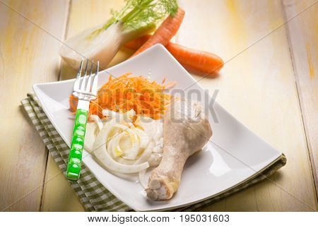 boiled chicken leg wit fennel and carrot salad, selective focus