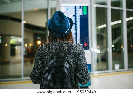 Young girl traveler with a backpack in a hat looks at the information board at the airport. Getting information about the flight.