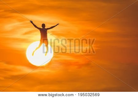 A bouncing man against the background of the sun and the setting sun. Concept of freedom rest summer holidays