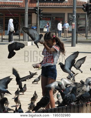 Sarajevo, Bosnia and Herzegovina - June 25, 2017: The girl feeds herd of pigeons on the market