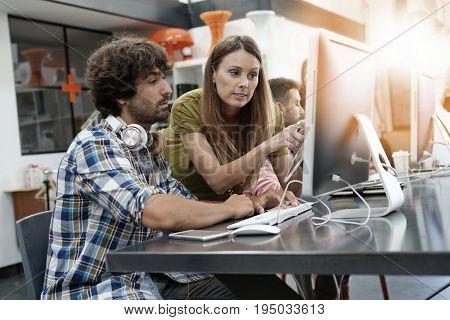 Co-workers in office working on project in desktop